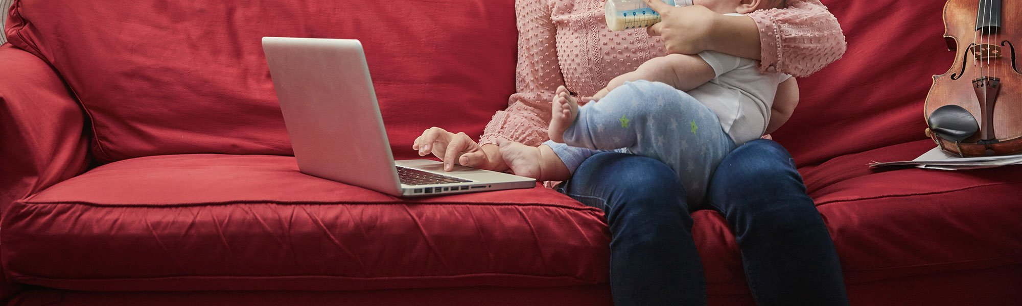 Mother on couch holding a baby and using a laptop