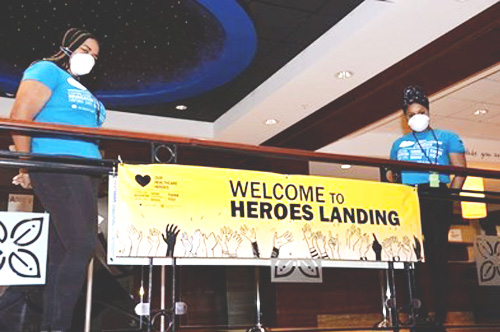 Two sefcu employees standing by heroes landing banner